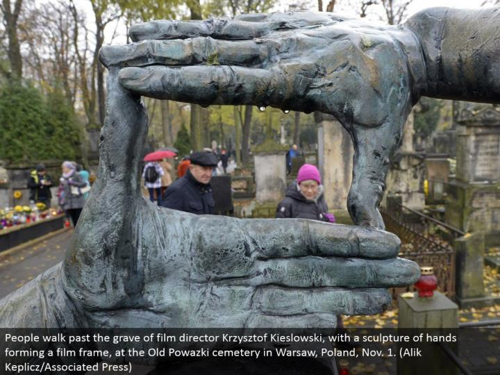 People stroll past the grave of film executive Krzysztof Kieslowski, with a figure of hands shaping a film outline, at the Old Powazki burial ground in Warsaw, Poland, Nov. 1. (Alik Keplicz/Associated Press)