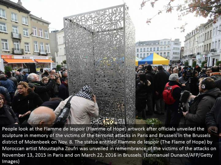 People take a gander at the Flamme de lespoir (Flamme of Hope) craftsmanship after authorities uncovered the figure in memory of the casualties of the psychological oppressor assaults in Paris and Brussels in the Brussels area of Molenbeek on Nov. 8. The statue entitled Flamme de lespoir (The Flame of Hope) by Moroccan craftsman Moustapha Zoufri was disclosed in recognition of the casualties of the assaults on November 13, 2015 in Paris and on March 22, 2016 in Brussels. (Emmanuel Dunand/AFP/Getty Images)