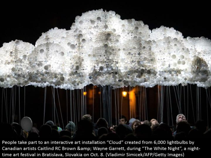 "People participate to an intuitive craftsmanship establishment ""Cloud"" made from 6,000 lights by Canadian craftsmen Caitlind RC Brown & Wayne Garrett, amid ""The White Night"", an evening workmanship celebration in Bratislava, Slovakia on Oct. 8. (Vladimir Simicek/AFP/Getty Images)"