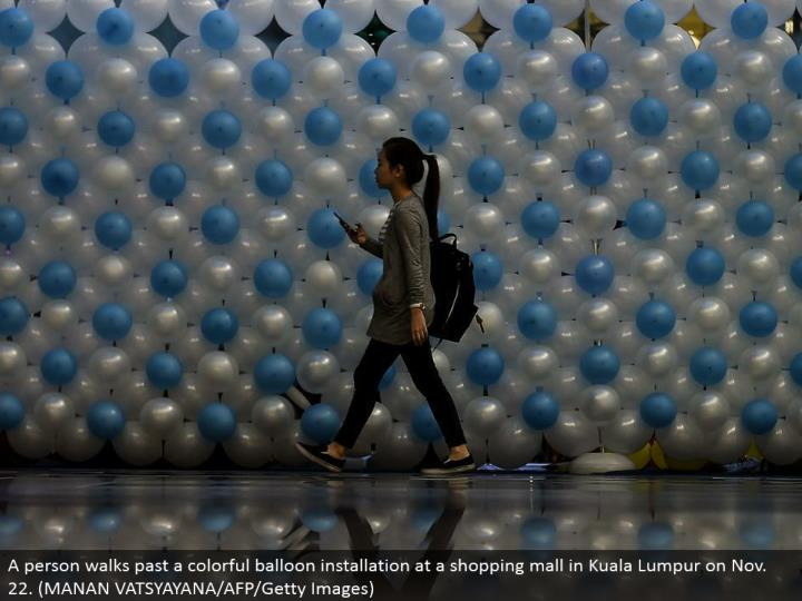 A individual strolls past a bright inflatable establishment at a shopping center in Kuala Lumpur on Nov. 22. (MANAN VATSYAYANA/AFP/Getty Images)