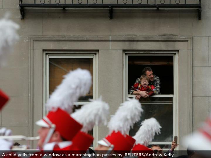A kid hollers from a window as a walking boycott cruises by. REUTERS/Andrew Kelly