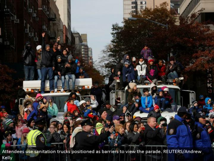Attendees utilize sanitation trucks situated as obstructions to see the parade. REUTERS/Andrew Kelly