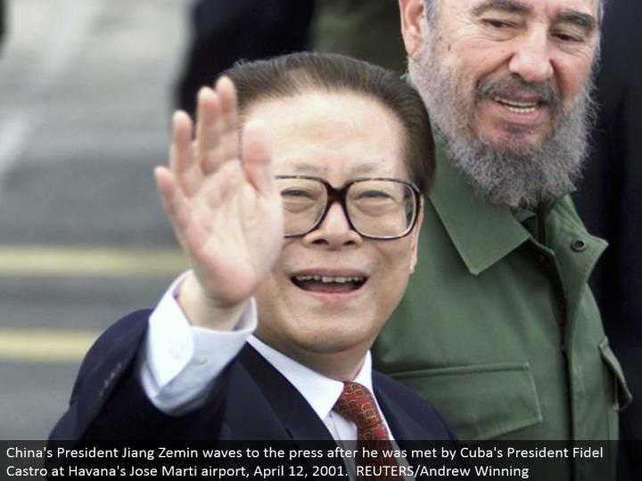 China's President Jiang Zemin waves to the press after he was met by Cuba's President Fidel Castro at Havana's Jose Marti airplane terminal, April 12, 2001. REUTERS/Andrew Winning