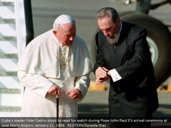 Cuba's pioneer Fidel Castro stops to peruse his watch amid Pope John Paul II's entry function at Jose Marti Airport, January 21, 1998. REUTERS/Zoraida Diaz