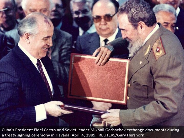 Cuba's President Fidel Castro and Soviet pioneer Mikhail Gorbachev trade archives amid a bargain marking service in Havana, April 4, 1989. REUTERS/Gary Hershorn