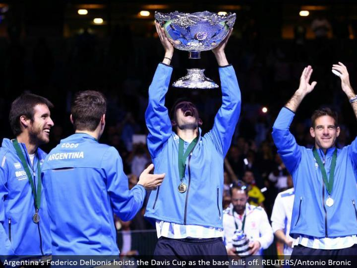 Argentina's Federico Delbonis lifts the Davis Cup as the base tumbles off. REUTERS/Antonio Bronic