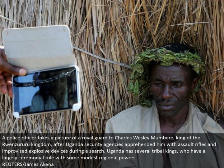 A cop takes a photo of an imperial monitor to Charles Wesley Mumbere, ruler of the Rwenzururu kingdom, after Uganda security offices caught him with ambush rifles and ad libbed hazardous gadgets amid a hunt. Uganda has a few tribal lords, who have a to a great extent stately part with some unobtrusive territorial forces.  REUTERS/James Akena