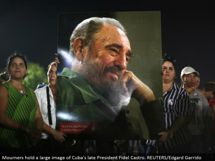 Mourners hold an expansive picture of Cuba's late President Fidel Castro. REUTERS/Edgard Garrido