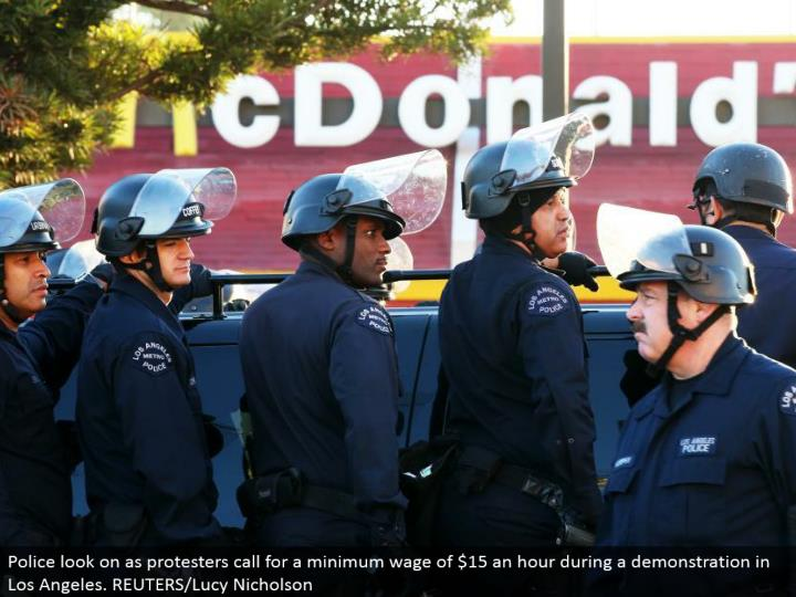 Police look on as dissenters require a lowest pay permitted by law of $15 a hour amid an exhibit in Los Angeles. REUTERS/Lucy Nicholson
