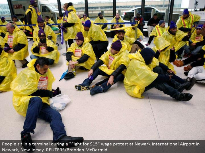 "People sit in a terminal amid a ""Battle for $15"" wage dissent at Newark International Airport in Newark, New Jersey. REUTERS/Brendan McDermid"