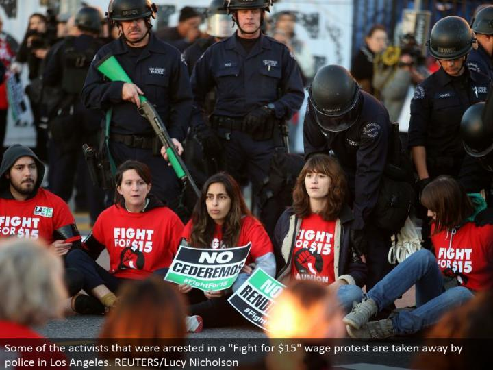 "Some of the activists that were captured in a ""Battle for $15"" wage dissent are taken away by police in Los Angeles. REUTERS/Lucy Nicholson"