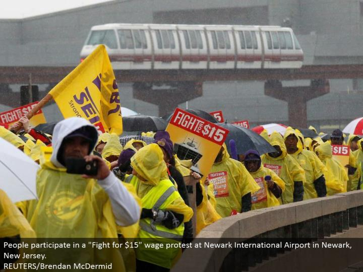 "People take an interest in a ""Battle for $15"" wage dissent at Newark International Airport in Newark, New Jersey.  REUTERS/Brendan McDermid"