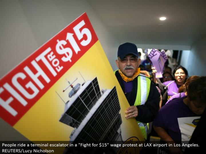 "People ride a terminal lift in a ""Battle for $15"" wage dissent at LAX air terminal in Los Angeles. REUTERS/Lucy Nicholson"