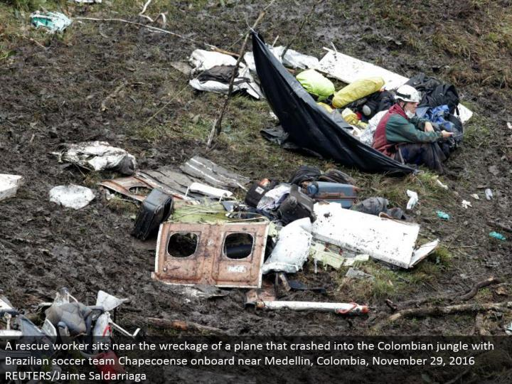 A safeguard specialist sits close to the destruction of a plane that collided with the Colombian wil...
