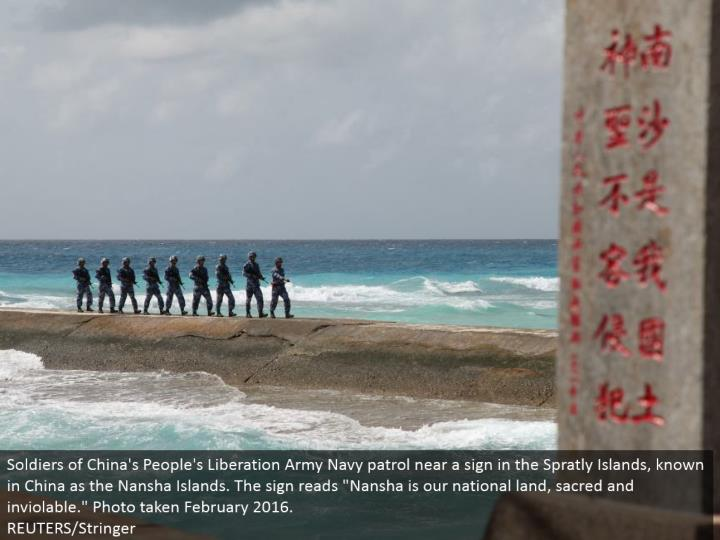 "Soldiers of China's People's Liberation Army Navy watch almost a sign in the Spratly Islands, referred to in China as the Nansha Islands. The sign peruses ""Nansha is our national land, hallowed and sacred."" Photo taken February 2016.  REUTERS/Stringer"