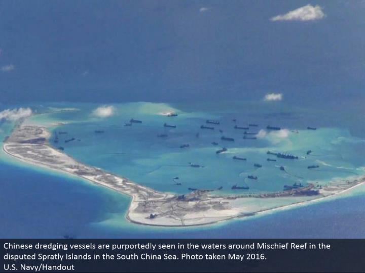 Chinese digging vessels are purportedly found in the waters around Mischief Reef in the debated Spratly Islands in the South China Sea. Photograph taken May 2016.  U.S. Naval force/Handout