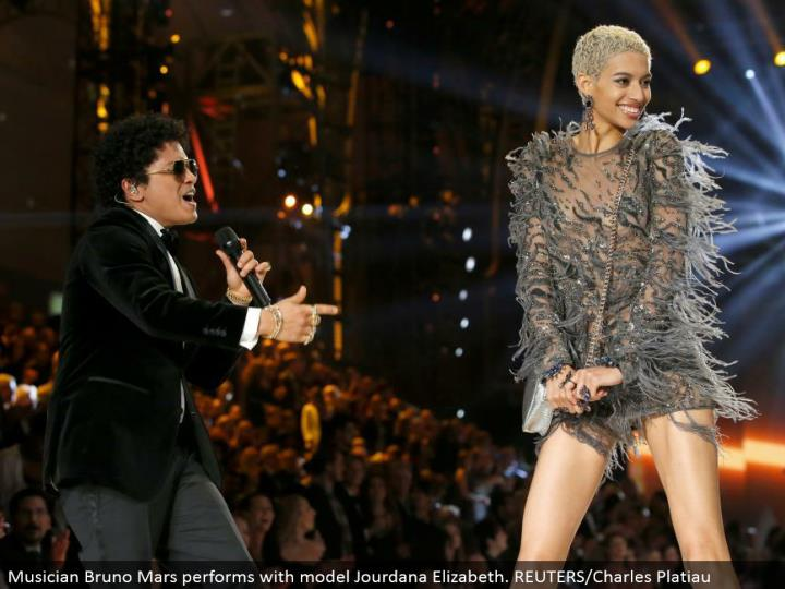 Musician Bruno Mars performs with model Jourdana Elizabeth. REUTERS/Charles Platiau