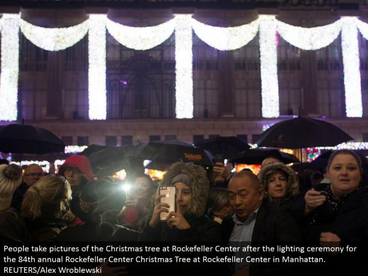 People take photos of the Christmas tree at Rockefeller Center after the lighting function for the 84th yearly Rockefeller Center Christmas Tree at Rockefeller Center in Manhattan. REUTERS/Alex Wroblewski
