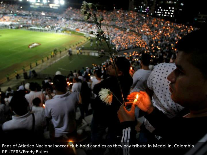 Fans of Atletico Nacional soccer club hold candles as they pay tribute in Medellin, Colombia. REUTERS/Fredy Builes