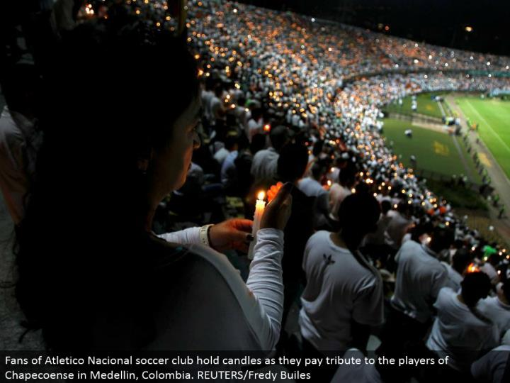 Fans of Atletico Nacional soccer club hold candles as they pay tribute to the players of Chapecoense in Medellin, Colombia. REUTERS/Fredy Builes