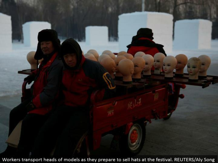 Workers transport heads of models as they plan to offer caps at the celebration. REUTERS/Aly Song