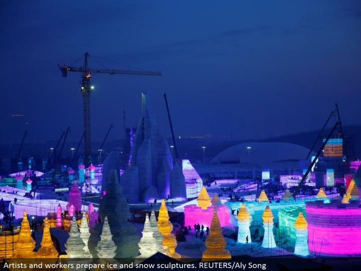 Artists and laborers get ready ice and snow figures. REUTERS/Aly Song