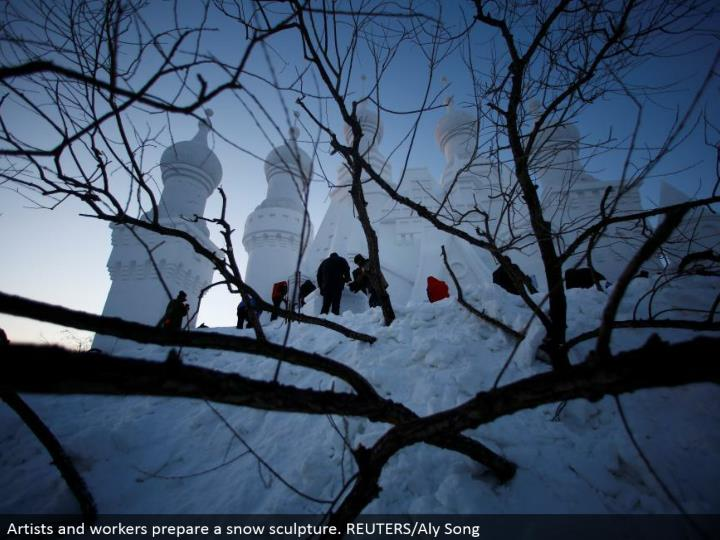 Artists and laborers set up a snow design. REUTERS/Aly Song