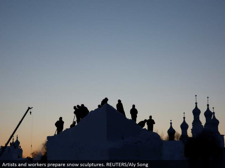 Artists and laborers get ready snow figures. REUTERS/Aly Song