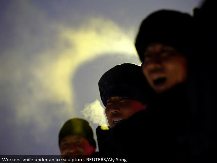 Workers grin under an ice mold. REUTERS/Aly Song