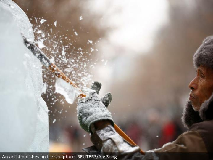 An craftsman cleans an ice design. REUTERS/Aly Song