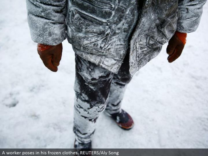 A laborer postures in his solidified garments. REUTERS/Aly Song
