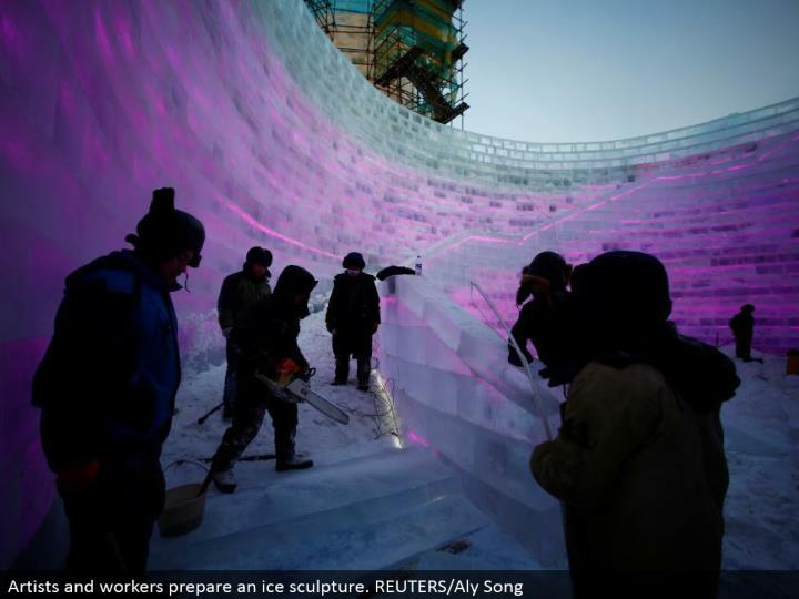 Artists and laborers set up an ice design. REUTERS/Aly Song