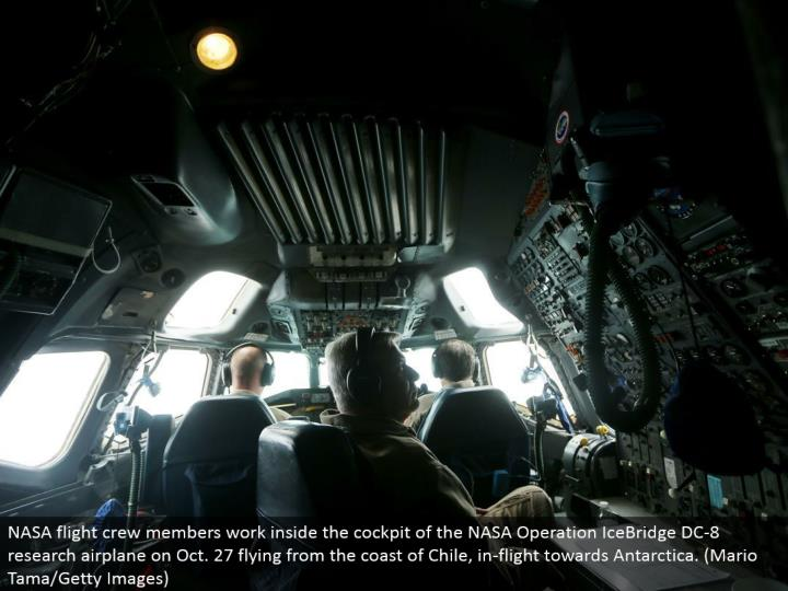 NASA flight group individuals work inside the cockpit of the NASA Operation IceBridge DC-8 look into plane on Oct. 27 flying from the shore of Chile, in-flight towards Antarctica. (Mario Tama/Getty Images)