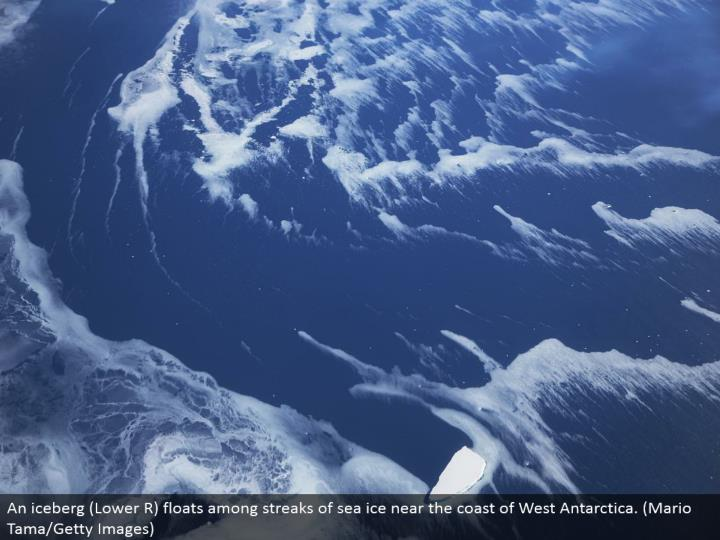 An icy mass (Lower R) skims among dashes of ocean ice close to the shore of West Antarctica. (Mario Tama/Getty Images)