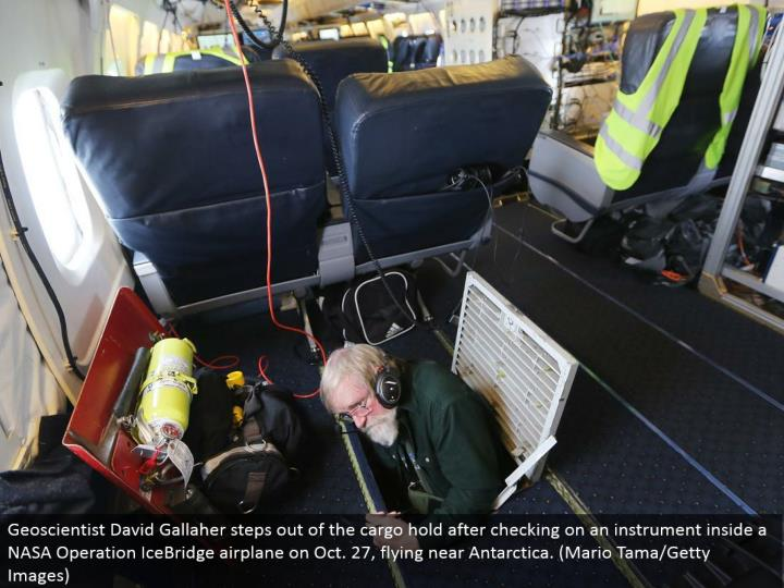 Geoscientist David Gallaher ventures out of the load hold in the wake of keeping an eye on an instrument inside a NASA Operation IceBridge plane on Oct. 27, flying close Antarctica. (Mario Tama/Getty Images)