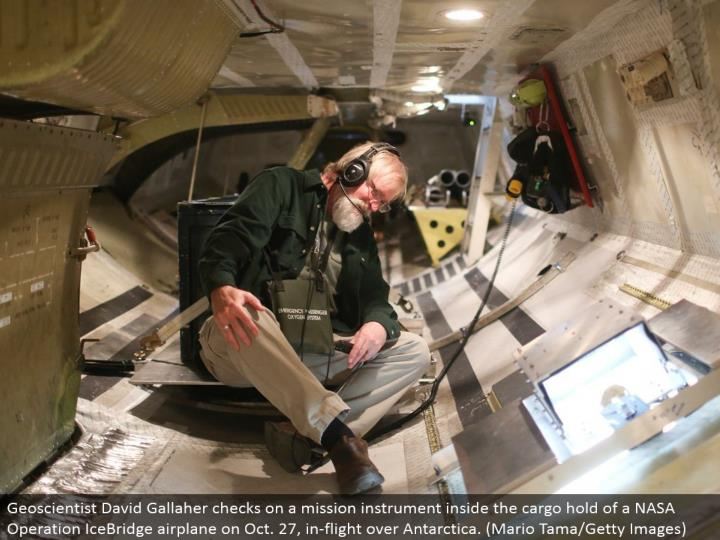 Geoscientist David Gallaher keeps an eye on a mission instrument inside the load hold of a NASA Operation IceBridge plane on Oct. 27, in-flight over Antarctica. (Mario Tama/Getty Images)