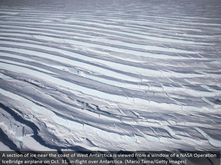 A segment of ice close to the shore of West Antarctica is seen from a window of a NASA Operation Ice...
