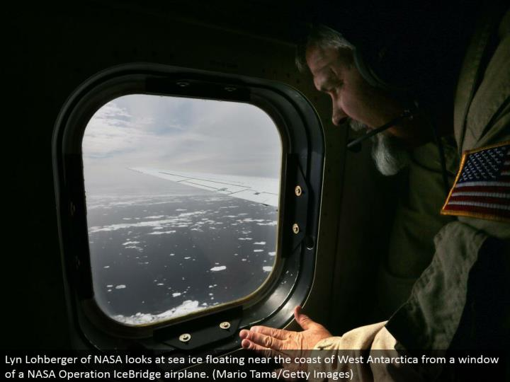 Lyn Lohberger of NASA takes a gander adrift ice drifting close to the shoreline of West Antarctica from a window of a NASA Operation IceBridge plane. (Mario Tama/Getty Images)