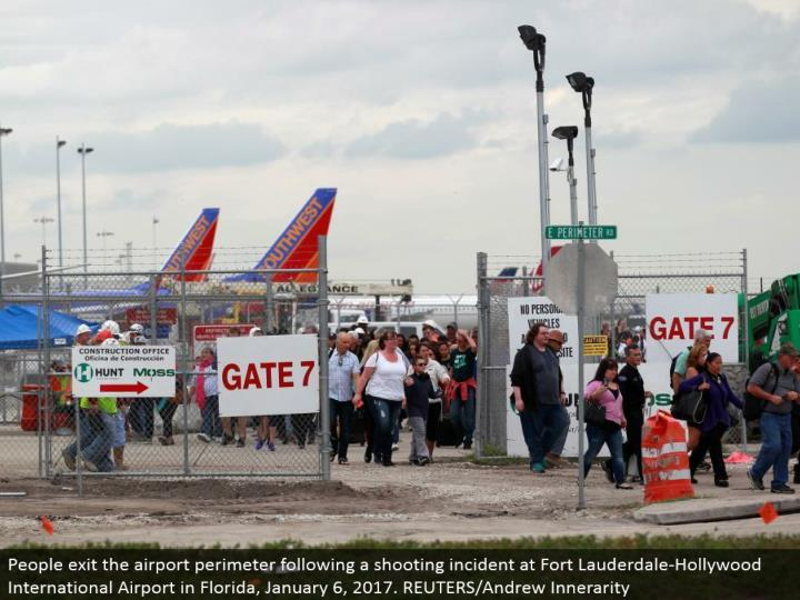 People leave the airplane terminal border taking after a shooting occurrence at Fort Lauderdale-Holl...