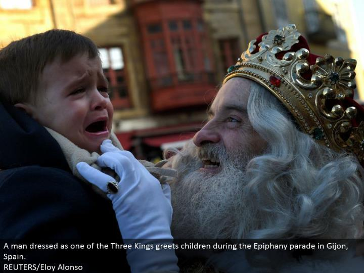 A man dressed as one of the Three Kings welcomes youngsters amid the Epiphany parade in Gijon, Spain.  REUTERS/Eloy Alonso