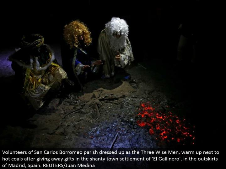 Volunteers of San Carlos Borromeo ward spruced up as the Three Wise Men, warm up beside hot coals in the wake of giving endlessly endowments in the shanty town settlement of 'El Gallinero', in the edges of Madrid, Spain. REUTERS/Juan Medina