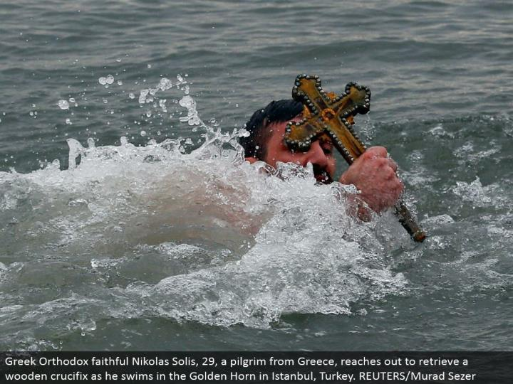 Greek Orthodox loyal Nikolas Solis, 29, a pioneer from Greece, connects with recover a wooden cross as he swims in the Golden Horn in Istanbul, Turkey. REUTERS/Murad Sezer