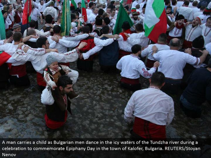 A man conveys a kid as Bulgarian men move in the frosty waters of the Tundzha waterway amid a festival to honor Epiphany Day in the town of Kalofer, Bulgaria. REUTERS/Stoyan Nenov