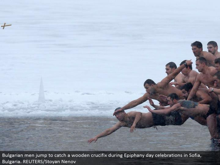 Bulgarian men bounce to discover a wooden cross amid Epiphany day festivities in Sofia, Bulgaria. RE...