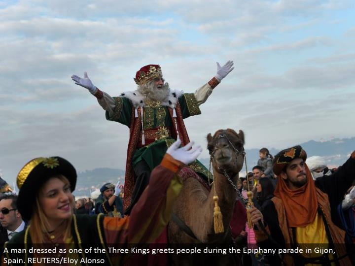 A man dressed as one of the Three Kings welcomes individuals amid the Epiphany parade in Gijon, Spain. REUTERS/Eloy Alonso