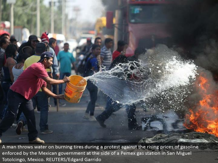 A man tosses water on smoldering tires amid a dissent against the rising costs of fuel upheld by the Mexican government along the edge of a Pemex service station in San Miguel Totolcingo, Mexico. REUTERS/Edgard Garrido