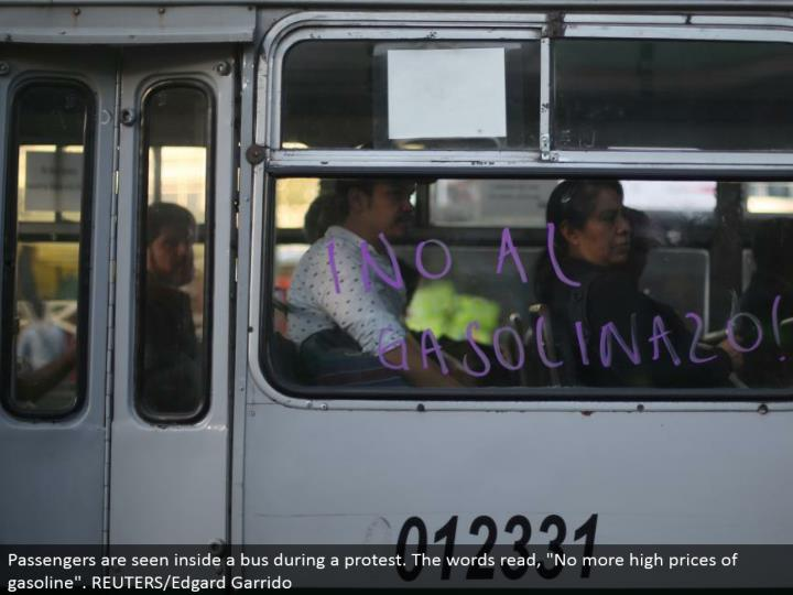 "Passengers are seen inside a transport amid a dissent. The words read, ""Not any more high costs of fuel"". REUTERS/Edgard Garrido"