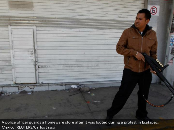 A cop monitors a homeware store after it was plundered amid a dissent in Ecatapec, Mexico. REUTERS/Carlos Jasso
