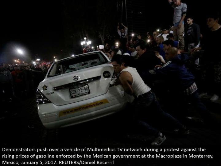Demonstrators push over a vehicle of Multimedios TV arrange amid a challenge against the rising cost...