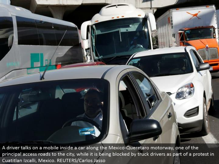 A driver chats on a versatile inside an auto along the Mexico-Queretaro motorway, one of the central get to streets to the city, while it is being obstructed by truck drivers as a component of a challenge in Cuatitlan Izcalli, Mexico. REUTERS/Carlos Jasso